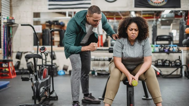 Gym with plus size black woman with natural hair with a man speaking to her in the gym.  Is he her trainer?  Or is this me getting pick up tips from my mentor on how to flirt at the gym?