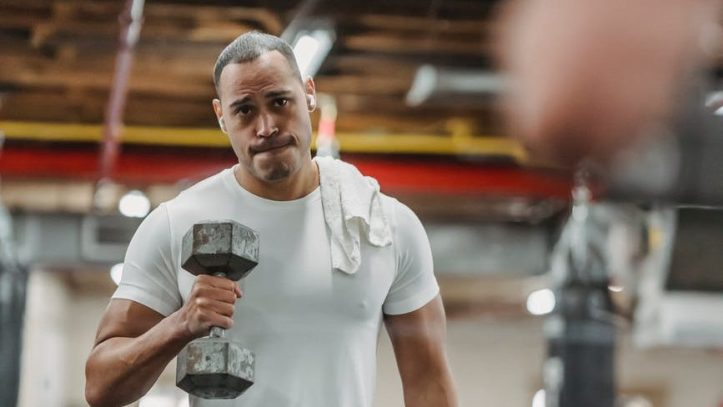 black sportsman training with dumbbells in gym.  Would you have the confidence to flirt at the gym with him?  How would you do it?
