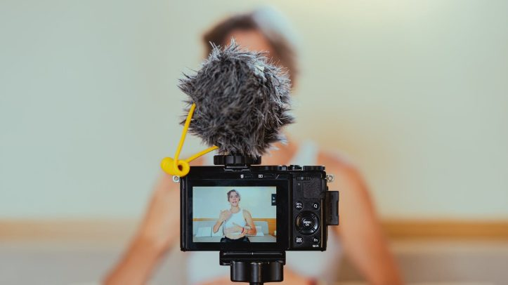 shallow focus photo of a video camera recording an elderly woman.  Why is every influencer and social media presence in any field suddenly weighing in with what they think about covid vaccines?