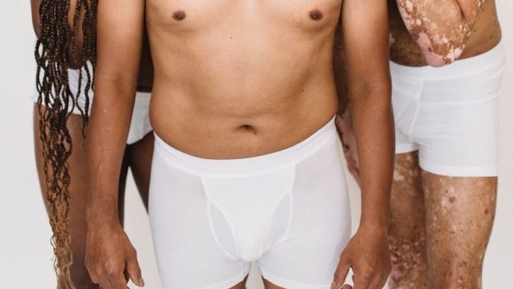 multiethnic men embracing against white background.  Mens underwear can be sold used on manthingsworn.com