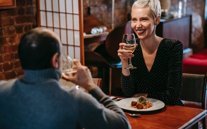 happy couple having date with wine and pasta in restaurant