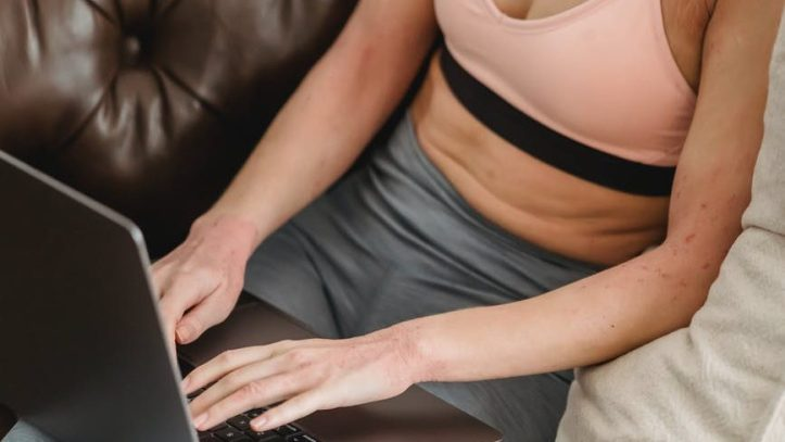 sporty woman browsing laptop on couch.  Is she making her allthingsworn.com profile as a seller?  Or maybe a buyer?