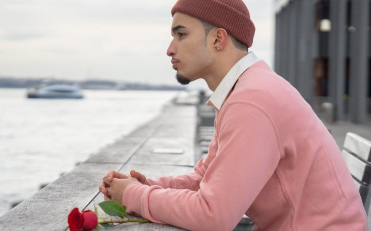 crop pensive man with red rose leaning on promenade railing