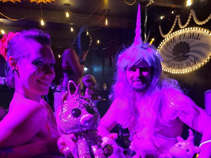 Billy King dressed as a unicorn and Carrie at the next table