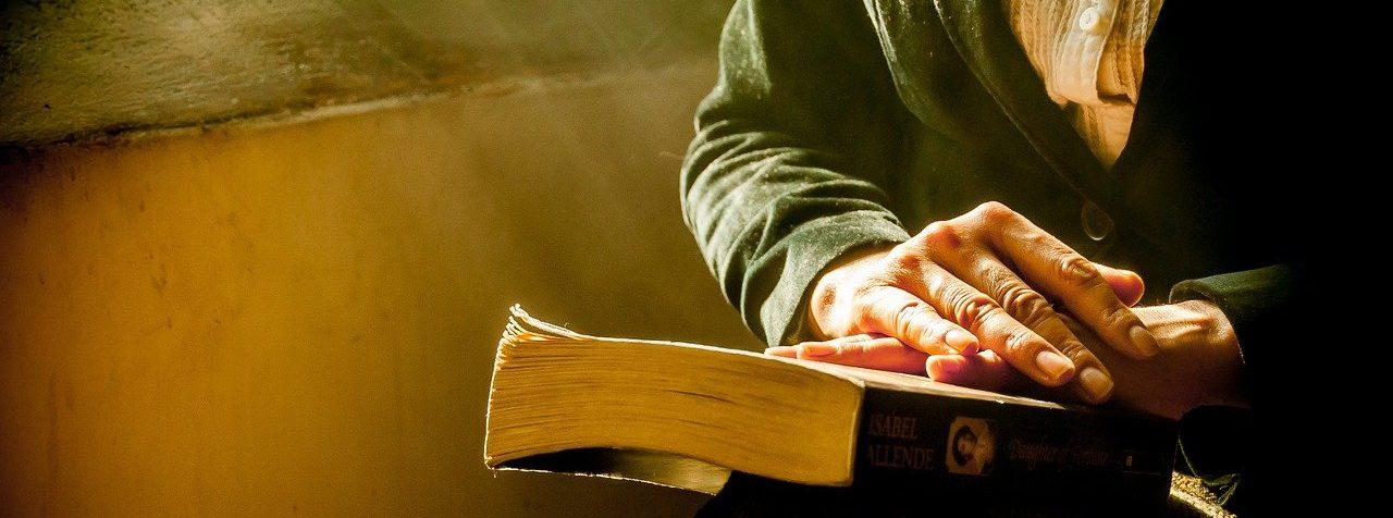 Durante la pausa le mani accarezzano il libro.