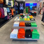 In Store Shirt Custom Displays With Shirts And Shorts Folded On Top Of Clothing Display Case In Center With Shirts And Sweatshirts Hanging ON Wall To Left And Right Sides