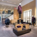 Retail Universal Custom Display UCD Showcasing Jackets With Mannequin Standing On Top Of Display Wearing Purple Jacket Jeans And High Heel Shoes