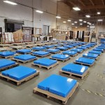 Universal Custom Display UCD PPE Clear Plastic Partition Barriers Laid Down On Top Of Blue Foam Inside Of Manufacturing Warehouse Floor Ready To Be Shipped And Delivered To Office Buildings