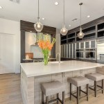 Universal Custom Display UCD Residential Custom Kitchen With Beautiful Stainless Steel Refrigerator With Multiple Ovens And Marble Island In Center Of Kitchen With Sink And Flowers Sitting On Counterspace