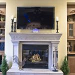 Universal Custom Display UCD Residential Custom Living Room With Large Fireplace In Center And Ornate Fireplace Mantel With Beautiful Wooden Shelves On Both Sides Of Fireplace Mantel