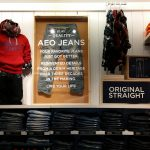 American Eagle In-Store Display Showcasing AEO Jeans On Clothing Racks With Jeans Stacked Folded Neatly With American Eagle Sweatshirts and And A Framed AEO Jeans Case Hanging On Wall