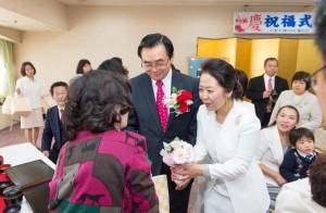 祝賀会で参加者に記念品を手渡す宋総会長ご夫妻
