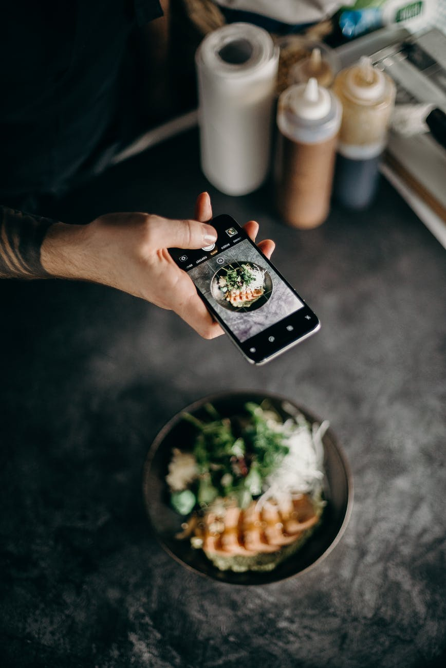 person taking photo of dish in bowl