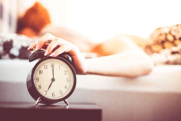 woman-shutting-off-ringing-alarm-clock-from-bed-picjumbo-com-5b749e7646e0fb0050e6f053