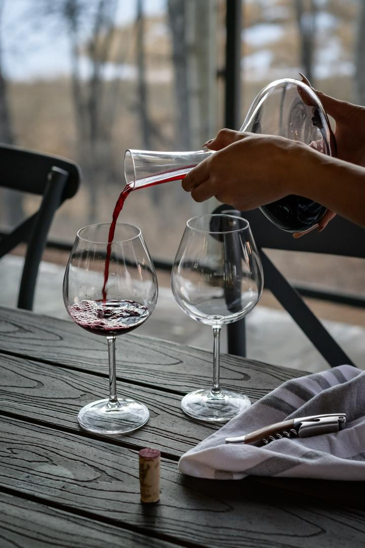 Pouring red wine from a decanter into a glass