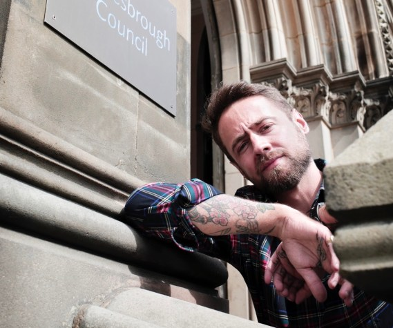 """This image is taken from below. Thomas Smith wears a plaid shirt, sleeves rolled up to just below the elbow. His right arm rests on the ledge outside a building. The sign above reads """"...brough Council"""". He squints slightly in the light, and has tattoos on his forearm."""