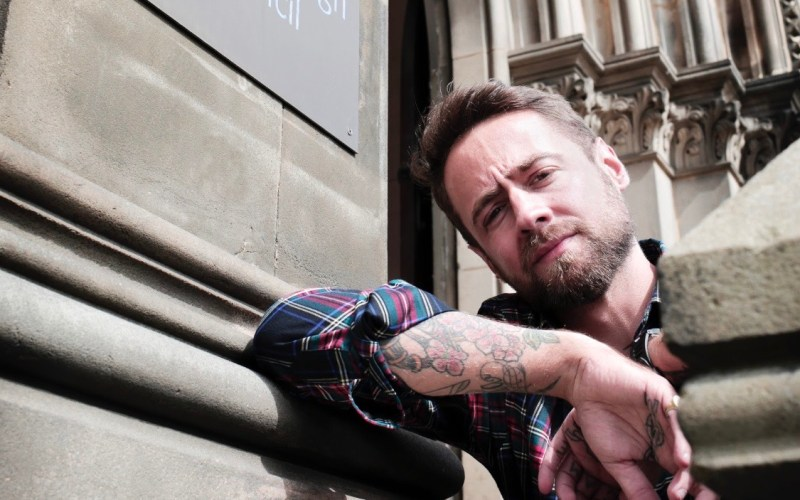 "This image is taken from below. Thomas Smith wears a plaid shirt, sleeves rolled up to just below the elbow. His right arm rests on the ledge outside a building. The sign above reads ""...brough Council"". He squints slightly in the light, and has tattoos on his forearm."