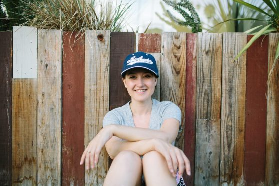 "Camille Thornton-Alson sits with her knees up, arms crossed across the top of her knees. She wears a navy hat that reads ""Los Angeles"" in white script. She leans against a wooden fence, and greenery grows overhead. She is smiling, and it is daytime."