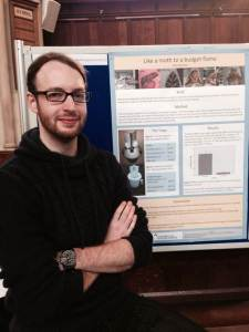 Tom with his prize-winning poster. The use of a bold, clear design and concise writing to convey detailed scientific content were key to its success.