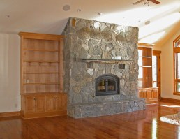 Alder side cabinets flanking a stone fireplace