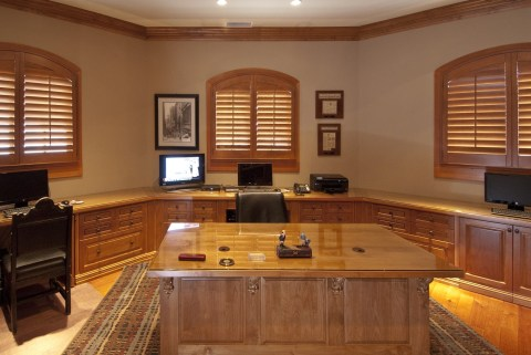 Alder wood office cabinetry with glass covered counter tops