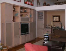 Gray washed Maple wood wall unit to house TV; speakers; AV units. Matching bar at the end.