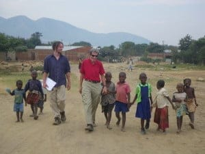 Kasese and another man walking with small children from an African village with a mountain in the background