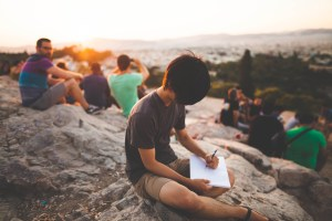 Teenage or young adult-aged boy writing or drawing in a journal or sketch book alone while a group sits nearby
