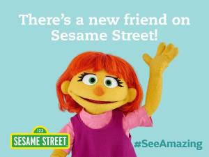 "A marketing image from Sesame Street of Julia, a new muppet on the autism spectrum. She is wearing a pink shirt and jumper, waving gesture with a smile. Above her are the words ""There's a new friend on Sesame Street!"" in white lettering. Bottom right, the words # see amazing in turquoise."
