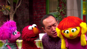 Scene from the new Sesame Street episode introducing Julia. Abby, Elmo, and a human friend look at Julia with concern, while she covers her ears with her hands.