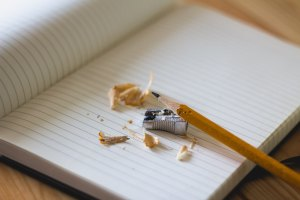 Image of a freshly sharpened pencil and a blank notebook. Pencil shavings are laying on the blank page.