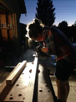 Young woman using circular saw with cool backlighting at night