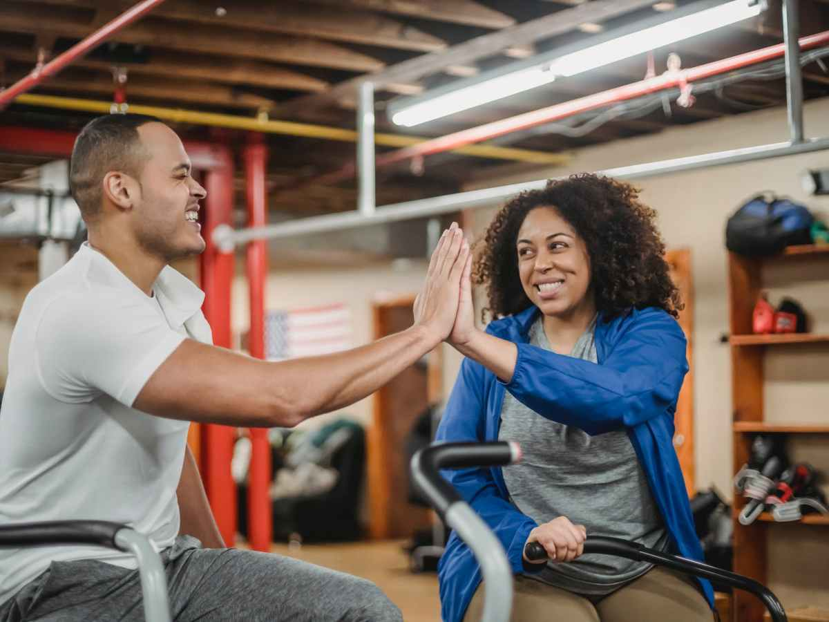 happy multiethnic sportspeople clapping hands in gym