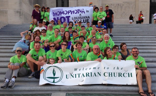 Group of people in green tshirts posing on steps
