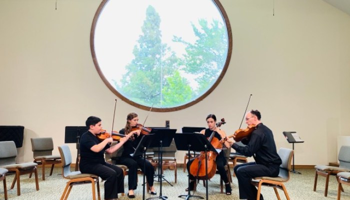 String quartet playing their instruments on a stage