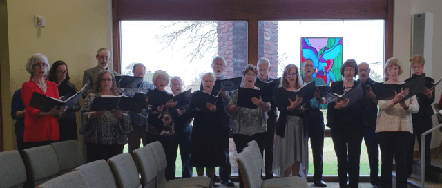 A choir singing in front of a window