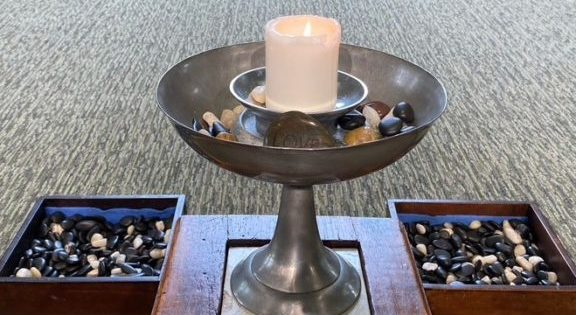 White candle burning in a silver chalice with multicolored pebbles in the chalice bowl