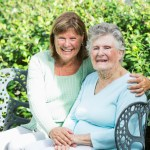 grandmother with adult daughter on bench cropped