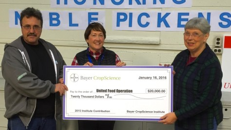 Connie Stewart, center, and Cliff Means present a check for $20,000 dollars from Bayer CropScience to support United Food Operation programs. Receiving the check is UFO Chairperson Elaine Harris.