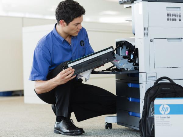 Managed Print Services - Technician changing toner cartridge on HP LaserJet Enterprise color flow MFP M575c