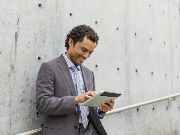 Man leaning against wall using a HP ElitePad 900.
