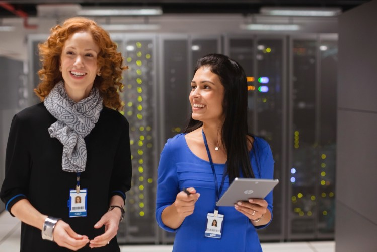 Two women in a data center using a HP Pro Slate 8 Tablet.