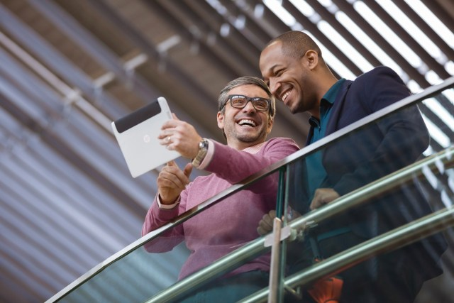 Two men using a HP ElitePad 900 while in the airport.
