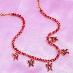 collier rouge papillon sur une table