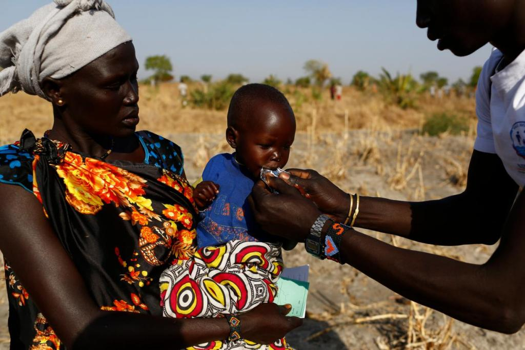 Angelina Nyanin hugs her malnourished niece as a UNICEF worker gives her Plumpy'nut , a peanut-based therapeutic food