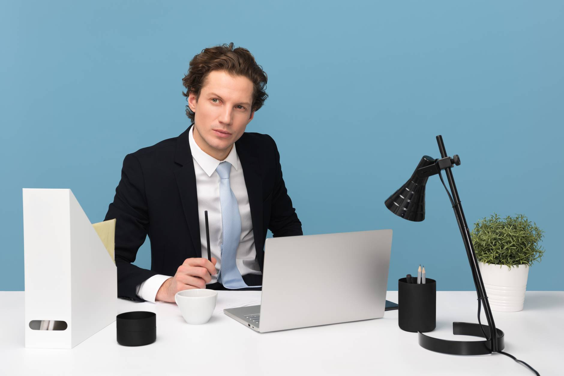 man sitting with laptop computer on desk and lamp.