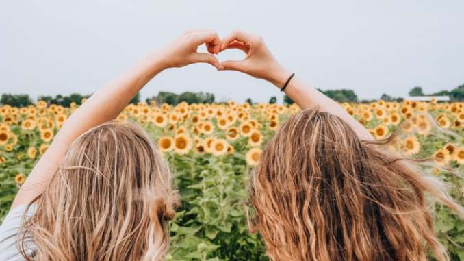 Two friends create a heart using their fingers. Universal symbol of love. Story about Friendship
