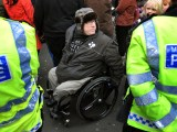 Disabled Man in Wheelchair surrounded by Met Police