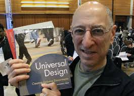 Ed Steinfeld holding his book next to his face.