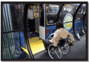A person in a manual wheelchair is entering onto the short yellow ramp into the bus from the tube shaped bus shelter